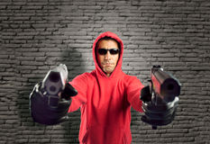 Robber pointing two guns. Delinquent man pointing two guns on a wall background Stock Photos