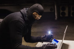 Robber shopping online while making light Royalty Free Stock Photography