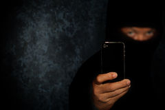 Robber with smartphone. Evil criminal with black smartphone phone ready for robbery or to commit a homicide royalty free stock photography