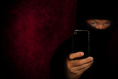 Robber with smartphone. Evil criminal with black smartphone phone ready for robbery or to commit a homicide royalty free stock images