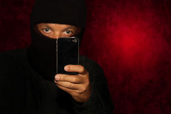 Robber with smartphone Royalty Free Stock Photos