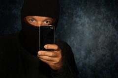 Robber with smartphone. Evil criminal with black smartphone phone ready for robbery or to commit a homicide royalty free stock photos