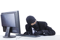 Robber steals information on computer Royalty Free Stock Images