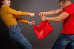 Robber takes bag. The girl is trying to prevent the robber who wants to pull the bag out of her hands stock images