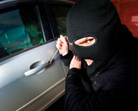 Robber and the thief in a mask hijacks the car Stock Image