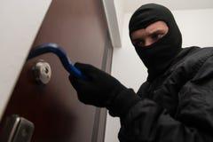 Robber Tries To Break In. Thief Burglar Force Lock Metal Door With A Tool During House Breaking Stock Image
