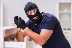 The robber wearing balaclava stealing valuable things. Robber wearing balaclava stealing valuable things royalty free stock images