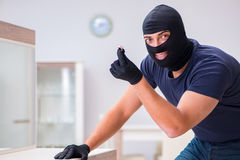 The robber wearing balaclava stealing valuable things Stock Photo