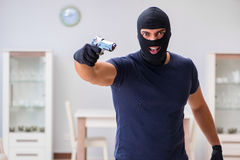 The robber wearing balaclava stealing valuable things Stock Image