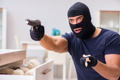 The robber wearing balaclava stealing valuable things Stock Images