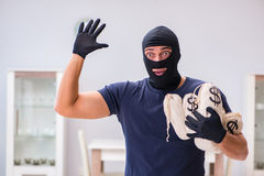 The robber wearing balaclava stealing valuable things Stock Photography