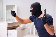The robber wearing balaclava stealing valuable things Stock Photos