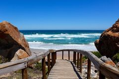 Robberg Nature Reserve. Landscape view of the rocks and blue ocean with wooden deck walkway for hiking leading to the sandy beach at Robberg Seal Mountain Nature Royalty Free Stock Photography