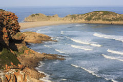 Robberg Plettenberg Bay. A scenic view Robberg Island.Sea cliffs with sparse green brush meet the rock-strewn sand and blue sea  A popular island destination for Stock Image