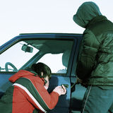 Robbery. Two crime guys breaking door of a car Stock Photos