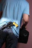 Robbery. Man with handgun tucked in belt leaving room carrying black bag Royalty Free Stock Photos