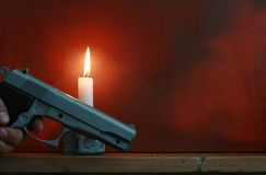 Robbery. Emotive shot of a hand holding a handgun next to a candle on a mantle piece shelf. Space for copy royalty free stock images