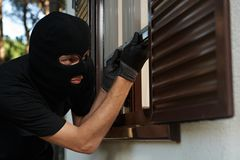 Robbery or burglary. break-in of an apartment. Thief in mask. Burglary or robbery. break-in of an apartment. Thief in mask opening the window Stock Images