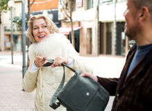 Robbery at day time. Male thief pulling bag at woman, outdoors robbery at day time Stock Photography