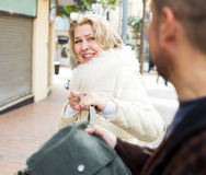 Robbery at day time. Mature male thief pulling bag at woman, outdoors robbery at day time Stock Image