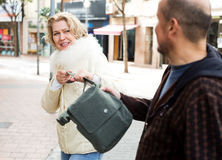 Robbery at day time. Senior male thief pulling bag at woman, outdoors robbery at day time Stock Photos