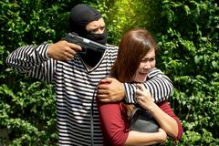 Robbery make a scared young Asian victim to walk alone in a lonely alley/Hostage of terrorist or burglar threatening with gun. Criminal concept stock images