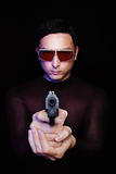 Robbery in the night. Criminal hitman in sunglasses pointing a gun in the dark with blue light reflection Royalty Free Stock Image