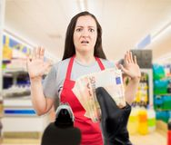Robbery at the supermarket. Portrait of saleswoman with arms up at the supermarket in an armed robbery Stock Photos