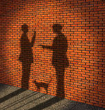 Robbing. One man threatens with a pistol to other man. (It is made in the form of a shade on a brick wall Stock Photography