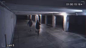 Robbing a girl talking on the phone in an underpass. Recording from a surveillance camera. View of dangerous situation in the underpass stock video footage
