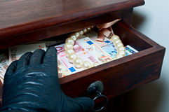 Robbing goods. Black leather glove reaching money euro and pearls in drawer Stock Image