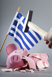 Robbing Greek piggy bank. Broken piggy bank with Greek flag and a hand holding a hammer - symbolic image for the dramatic financial crisis of the country Royalty Free Stock Photography