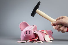 Robbing piggy bank with hammer Royalty Free Stock Photos