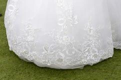 Robe blanche de jeune mariée d'ourlet avec la broderie sur l'herbe verte Photo libre de droits