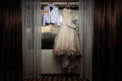 Robe blanche de mariage de luxe et accrocher uniforme d'insignes militaires Image stock