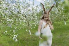 Robe blanche de port de belle fille blonde de l'adolescence avec les klaxons o de cerfs communs Photos libres de droits