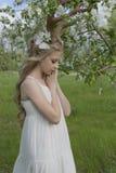 Robe blanche de port de belle fille blonde de l'adolescence avec les klaxons o de cerfs communs Image stock