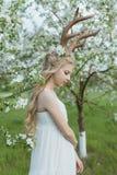 Robe blanche de port de belle fille blonde de l'adolescence avec les klaxons o de cerfs communs Images stock