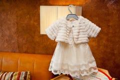 Robe blanche pour la fille accrochant sur les épaules dans l'intérieur photos libres de droits