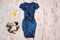 Robe bleue dans les paillettes, les chaussures noires et les moitiés de l'orange Fond en bois, concept à la mode Photographie stock libre de droits