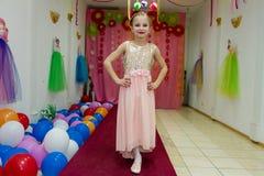 Robe d'expositions de petite fille et amusement de avoir Photo stock