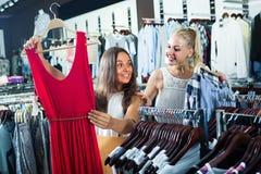 Robe de achat de deux filles dans la boutique de vêtements Photos libres de droits
