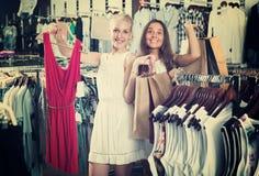 Robe de achat de deux filles dans la boutique de vêtements Photo libre de droits