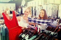 Robe de achat de deux filles dans la boutique de vêtements Images libres de droits