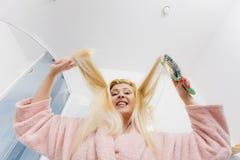 Robe de chambre de port de femme se brossant les cheveux Images libres de droits