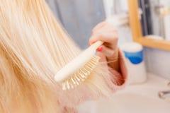 Robe de chambre de port de femme se brossant les cheveux Image libre de droits