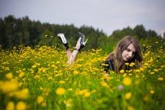 Robe de fille dans l'herbe avec des pissenlits Images stock