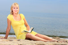 Robe de jaune de fille de livre de lecture de femme Photographie stock libre de droits