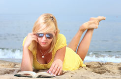 Robe de jaune de fille de livre de lecture de femme Images stock