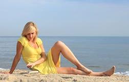 Robe de jaune de fille de livre de lecture de femme Photo stock